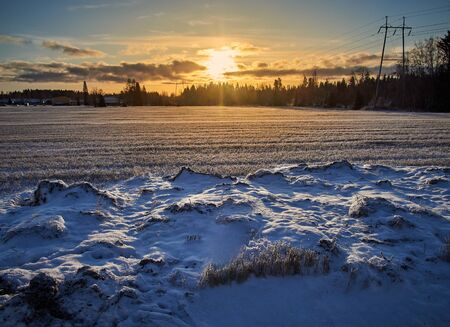 Dramatic winter wonderland scenery in scenic golden evening light at sunset with clouds in Finland, northern Europe
