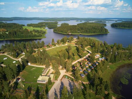 Aerial view of blue lake and green forests on a sunny summer day above a caravan camping site. Birds eye view drone photography. Ruovesi, Finland. Stock Photo