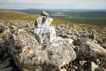 Beautiful stone stack and a view from a fell over forests, lakes and marshes of Lapland. Pallas-Yllastunturi National Park, Finland. Stock Photo