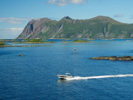 A boat leaving the famous tourist attraction Hamn Village, Senja island, Troms county - Norway Stock Photo