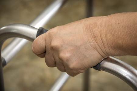 infirm: Hand of senior woman on a walker.