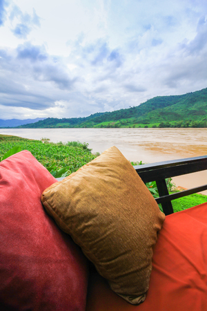 riverside trees: Two pillows and sofa on the balcony in the riverside room. Stock Photo