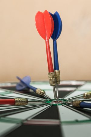 Darts hitting in the target center of dartboard. Stock Photo