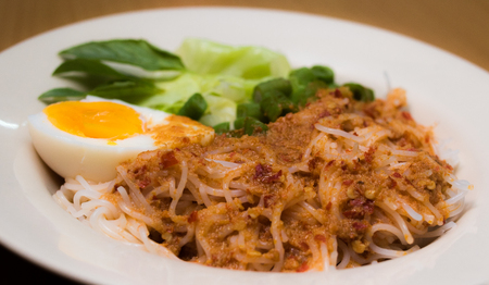Thai vermicelli eaten with curry in white dish.