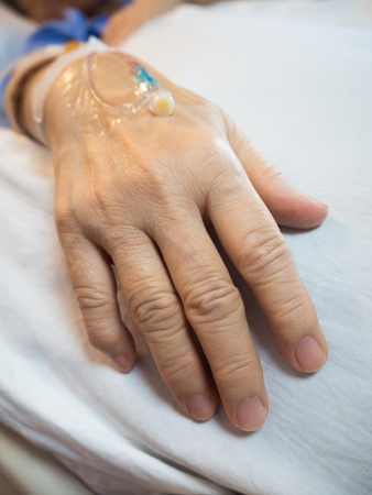 Left hand of the patient on clean bed in the hospital.
