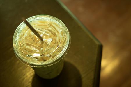 Eiskaffee Latte in Plastikbecher auf dem oberen Tisch, Farbe Vintage-Stil, selektiver Fokus