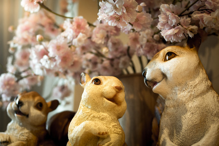 Three squirrel dolls on a table with pink flowers.