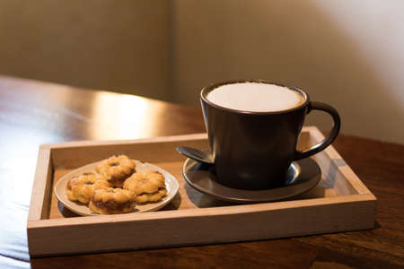Hot coffee in a ceramic cup on a wooden plate.