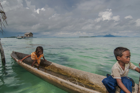 trawl: Sabah, Malaysia-July 10, 2016:Daily life of unidentified seagypsy fisherman people in Mabul Island, Malaysia. Seagypsy people is a nomadic and stay in the wooden boat or canoe.