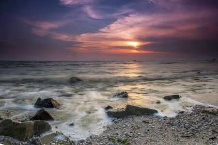 The majestic sunset captured at Pantai Jeram, Selangor, Malaysia. The motion of cloud and water is due to long exposure effect.
