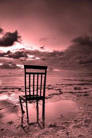 Lonely chair at beach during sunset