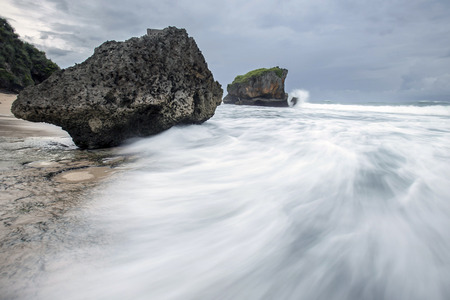 agitation: Sea waves crashing over rocks on the wild stone beach in sunset time and seafoam created by the agitation of seawater in the moment of ocean waves crashing against rocks. Stock Photo