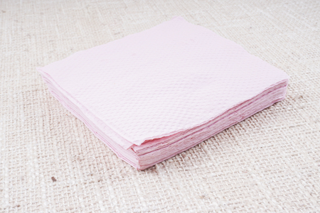 serviette: Pink napkin isolated on white background. Kitchen paper serviette. Clean food towel in restaurant. Single square shape object. Blank tablecloth on table. Domestic, cafe cloth.