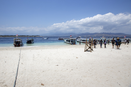 footprints in sand: Tropical sandy beach with buildings and boats in a sea. Gili Trawangan, Indonesia