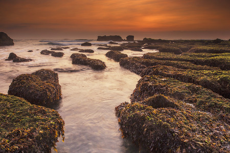 Sunset as seen from Mengening Beach, Bali,Indonesia. Mossy rocks in the foreground. Vibrant Colour. Stock Photo