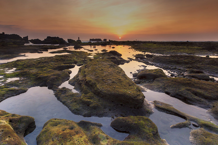vibrant colour: Sunset as seen from Mengening Beach, Bali,Indonesia. Mossy rocks in the foreground. Vibrant Colour. Stock Photo