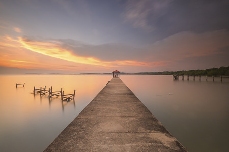 Perspective view of a wooden pier on the pond at sunset with perfectly specular reflection Stock Photo