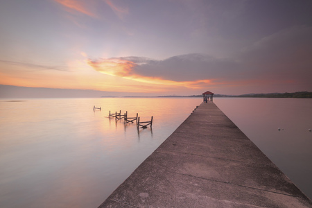 specular: Perspective view of a wooden pier on the pond at sunset with perfectly specular reflection Stock Photo