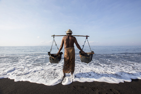 BALI, INDONESIA - May 8,2015 : Unidentified local people work as natural salt farmer at Kasumba Beach, Bali. He collecting sea water and make salt naturally.