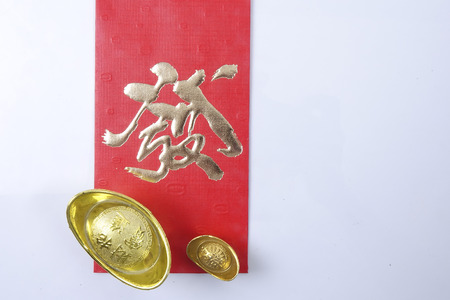 Chinese new year festival decorations, ang pow or red packet and gold ingots. Chinese characters means luck,wealth and prosperity. Stock Photo