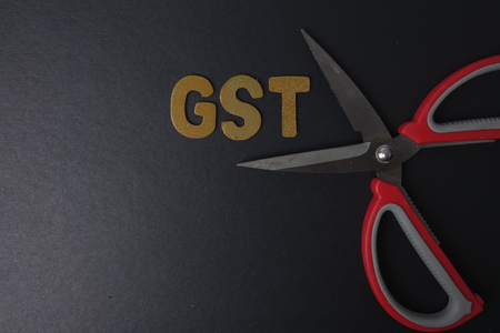 exemption: Scissors and word of GST on black background Stock Photo