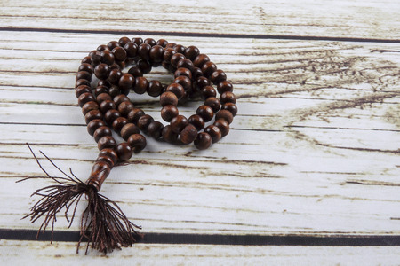 the wooden tasbih or rosary on wooden background. Stock Photo