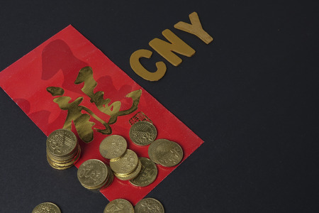 Chinese red packet with the Chinese phrase means Good luck and prosperity ,gold coins and wording of CNY. Chinese New Year Festival. Low light.