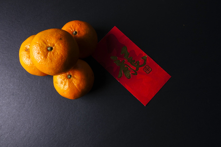 Chinese new year festival decorations,  red packets and mandarin oranges, golden Chinese letter means luck