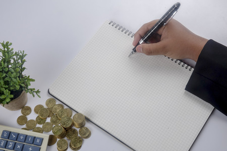 cash slips: Close-up Of A Businessman writing Report with Stack Of Coins Stock Photo