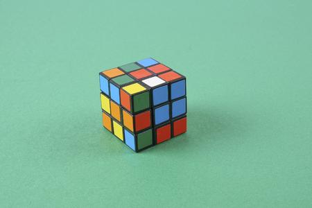 Kuala Lumpur, 24 February 2017.Rubik cube isolated on green background. Problem solving concept.