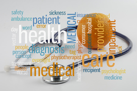 Orange and stethoscope with conceptual text cloud. Stock Photo