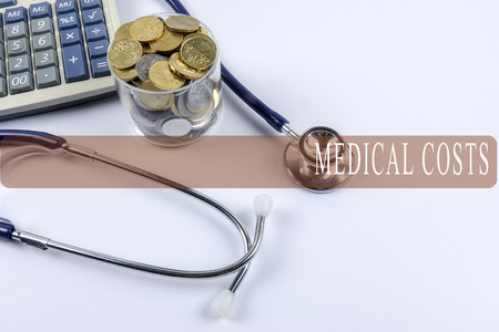 doctor money: a stethoscope with piles of coins and calculator - healthcare cost concept