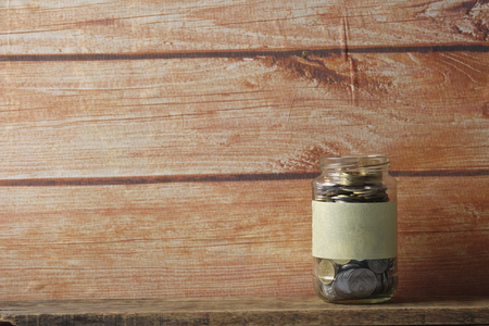 Coins in jar over wooden background. Saving concept Stock Photo