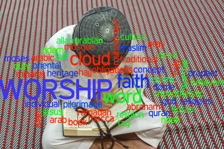 Boy reading al Quran with cloud words. Stock Photo