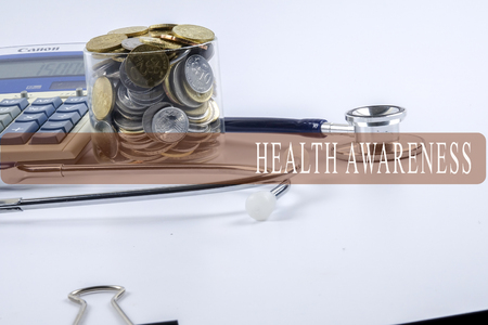 a stethoscope with piles of coins and calculator - healthcare cost concept