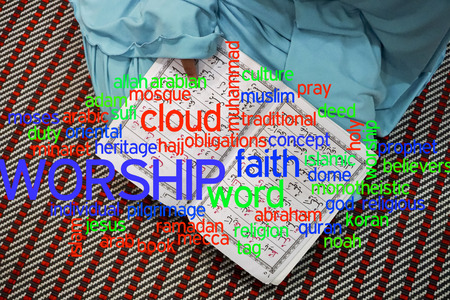holy book: Girl reading al Quran with cloud words. Stock Photo