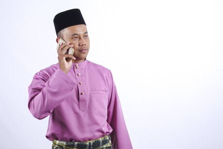 Man in traditional clothing with smartphone celebrate Eid Fitr. Stock Photo