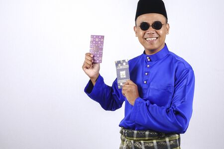 Man in traditional clothing cheerful with money packet during celebrate Eid Fitr.