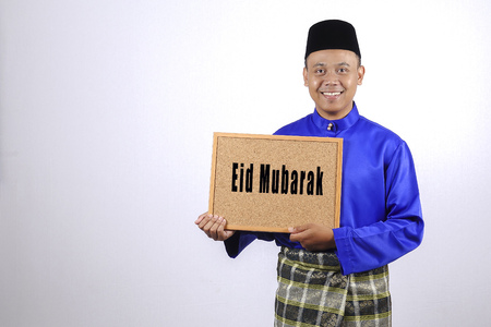 Young man smiling with chalkboard for Eid Fitr or Eid Adha celebrations. Stock Photo - 79931810