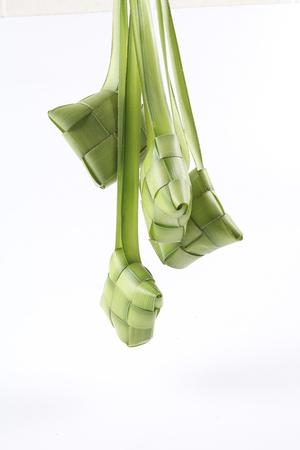 젊은 코코넛 잎으로 만든 쌀을 요리하기위한 천연 쌀 용기 인 Ketupat 만들기