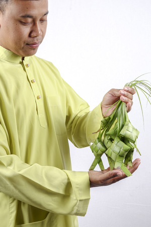 Young muslim adult holding rice dumpling during Eid Mubarak.