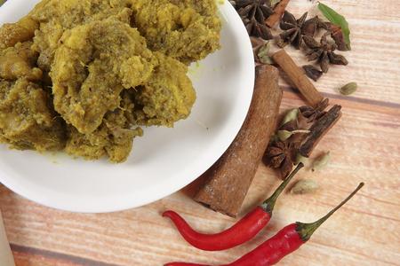 말레이시아 요리 Rendang Ayam 또는 건포도 카레 치킨과 Ketupat Nasi (쌀만 두) 나무 배경 위에