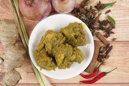 Malaysian dish Rendang Ayam or dry curry chicken and Ketupat Nasi (Rice Dumpling) over wooden background Stock Photo - 80552830