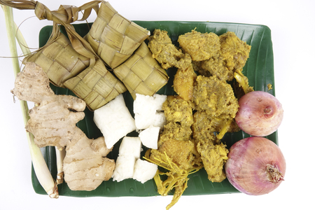 Malaysian dish Rendang Ayam or dry curry chicken and Ketupat Nasi (Rice Dumpling) over wooden background