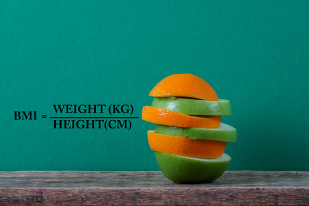 A conceptual fruit of fitness with green apple and orange and a measuring tape with BODY MASS INDEX (BMI) formula.