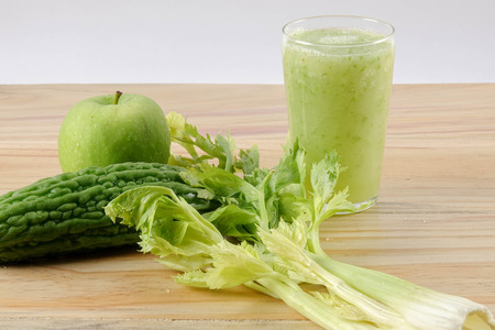 Green apple, bitter gout and celery isolated on wooden background to control diabetic naturally. Health concept.