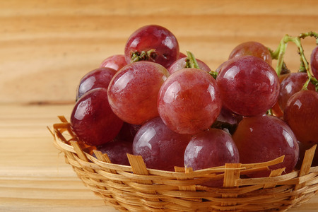 Red grape on the basket over wooded background.