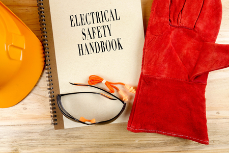 Safety hat,glove,glasses,ear plugs and note book with ELECTRICAL SAFETY HANDBOOK. Health and safety concept.