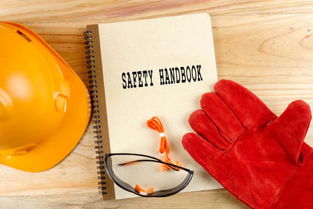 Safety hat,glove,glasses,ear plugs and note book with SAFETY HANDBOOK. Health and safety concept. Stock Photo