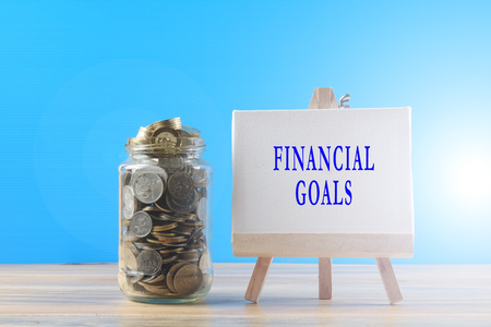Mason jar with coins and chalkboard with FINANCIAL GOALS words. Finance and saving concept. Lens flares added